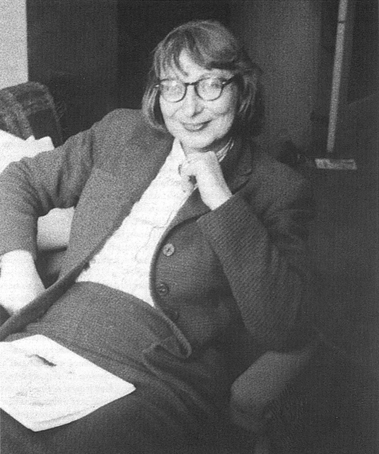Black and white portrait of Jane Jacobs. She wears a suit, her iconic glasses, and is seated.