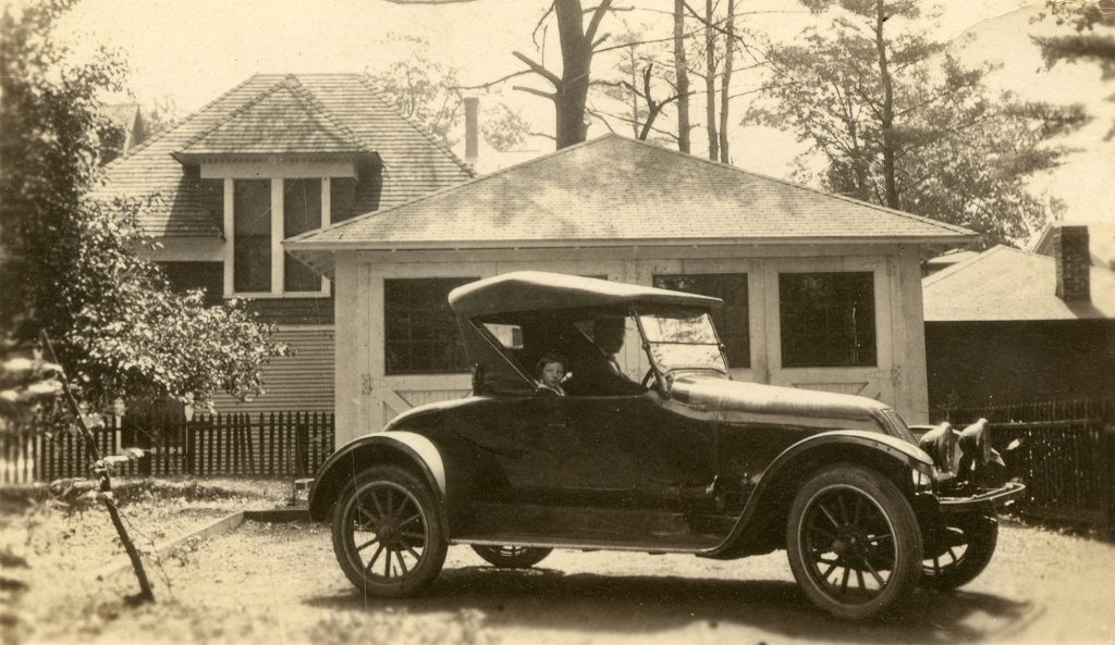 Black and white photo of Jane Jacobs in a black 1921 car.