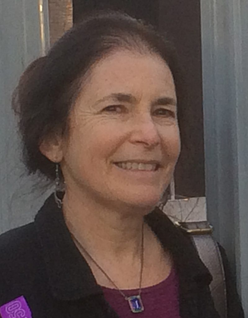 Photo of Glenna Lang, a white woman with brown hair pulled into a bun.
